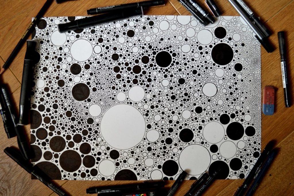 A completed piece of artwork by Cai Burton filling a large piece of paper. The artwork is a hyper-detailed patterning of circles of various sizes rendered in black and white. Around the piece of paper are the various pens that Cai has used to complete the image.