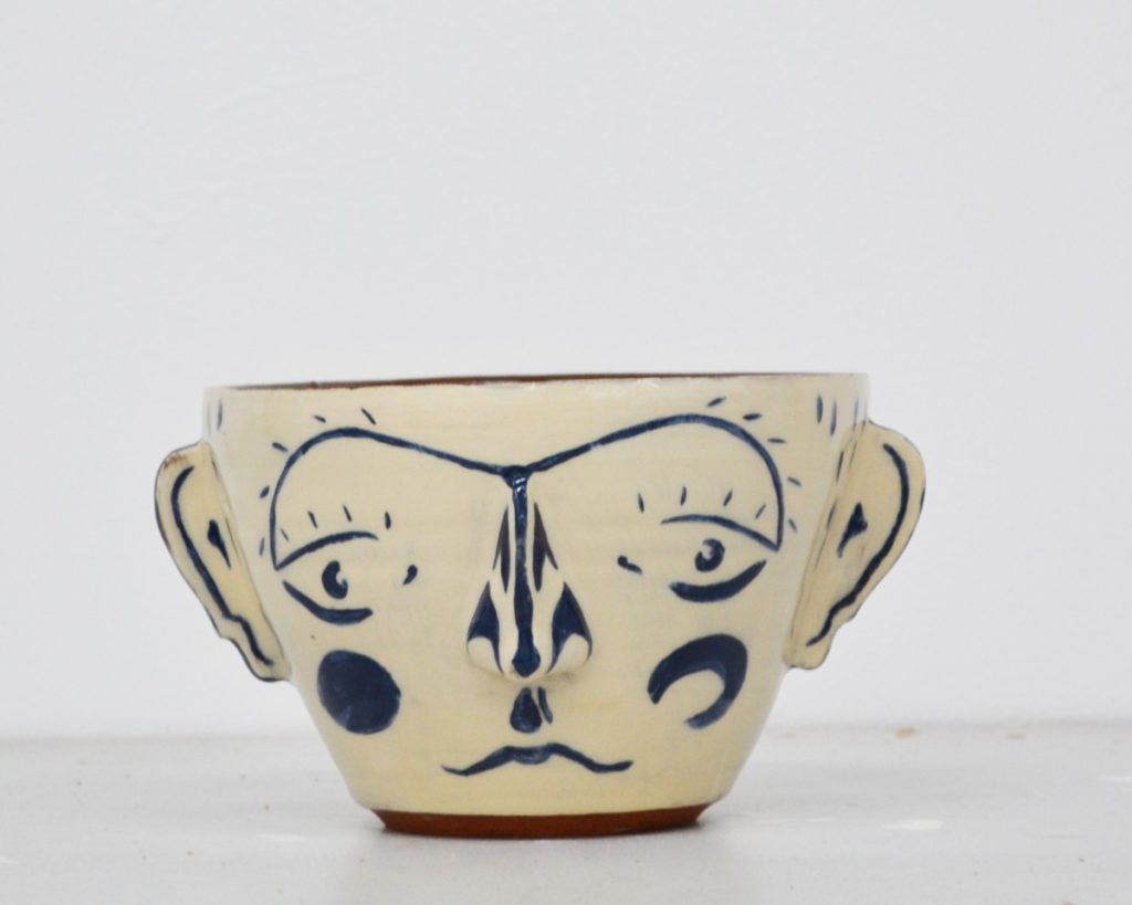 Pictured is a ceramic bowl from pottery line MareWares, the exterior of the bowl is white with blue facial features, ears protrude for either side of the bowl. The interior and base maintain the red colour of the clay.