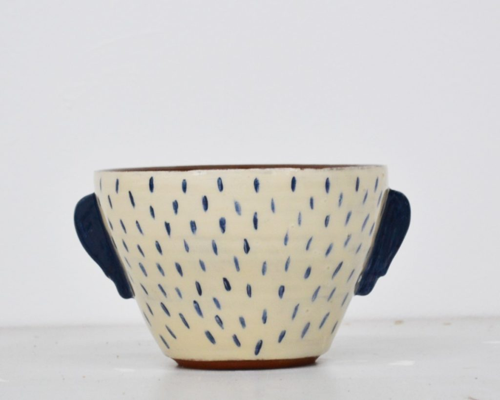 Pictured is a ceramic bowl from pottery line MareWares, hair is painted on the white exterior of the bowl as if we are viewing the back of a head, blue ears portrude from either side of the bowl, the exterior is white with blue detailing. The interior and base maintain the red colour of the clay.