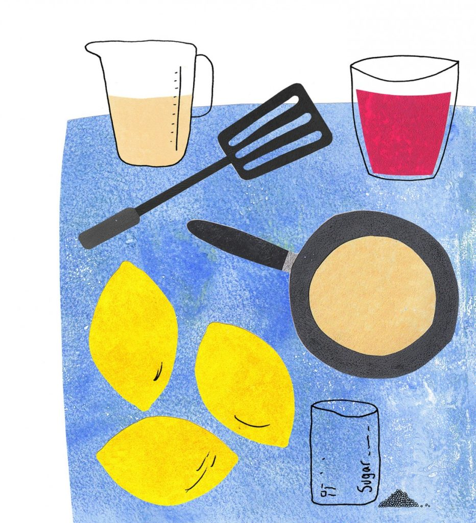 A blue table with pancake mixture on, including a frying pan, lemons and sugar