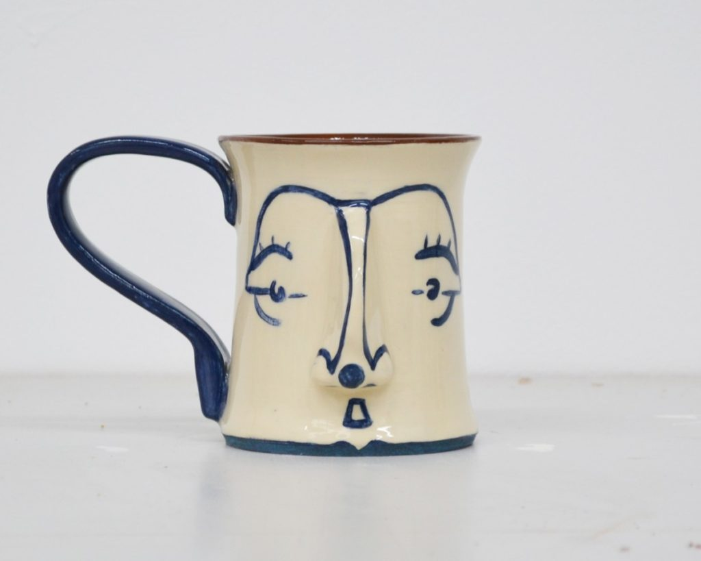 Pictured is a ceramic mug, taking the shape of a face. The mug is white and blue. It has a blue handle and blue facial features on top of the white body of the mug. The interior of the mug retains the red colour of the clay it is made from.