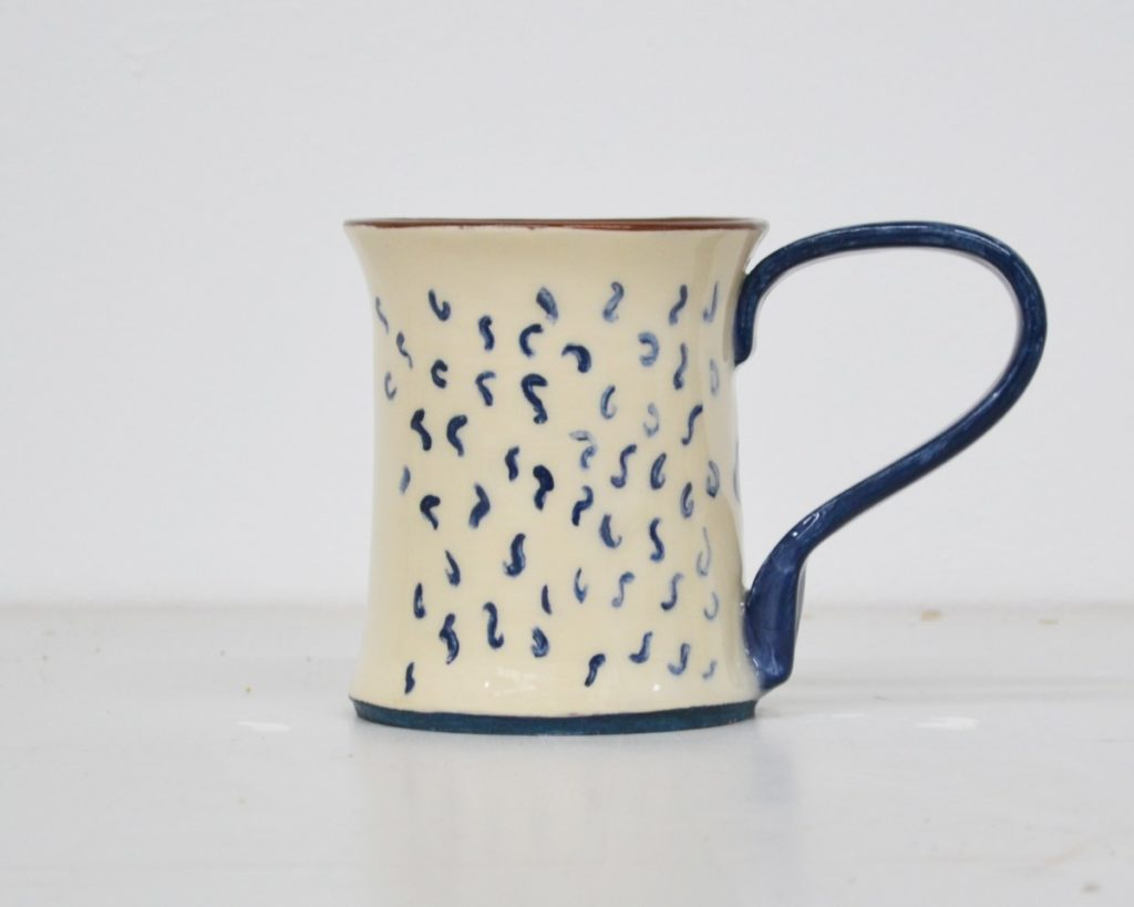Pictured is a ceramic mug from pottery line MareWares, hair is painted on the white exterior of the mug as if we are viewing the back of a head, a blue handle takes the shape of an ear on the side of the mug, the exterior is white with blue detailing. The interior and base maintain the red colour of the clay.