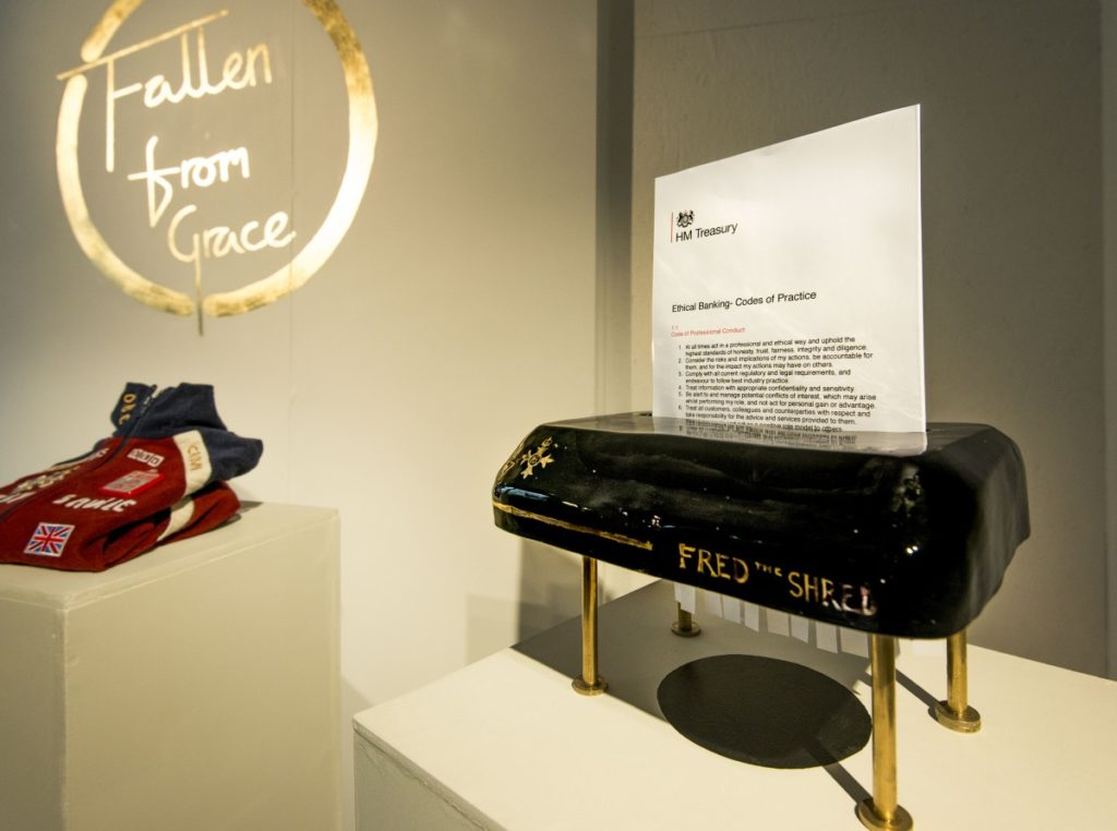 Pictured is two objects from the project Fallen from Grace. in the foreground to the left is the top of a black ceramic shredder sat upon for gold pillars. The front of the shredder reads Fred the Shred in gold lettering. A document on ethical banking, codes of practice is half shredded. In the background is a tracksuit top atop another plinth. Behind both is a gold sign in the style of the top of the pops logo, it reads Fallen from Grace, around these words a gold circle is drawn.