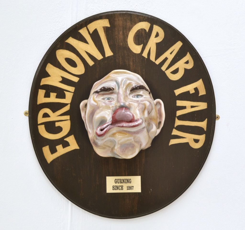 Pictured is a trophy celebrating a 'Gurning' competition. In the style of a hunting Trophy. A grotesque male ceramic head hangs on a dark wooden mount. Large gold lettering encircles the top half of the ceramic head, reading 'Egremont Crab Fair'. A small plaque sits below the head reading 'Guring since 1267'
