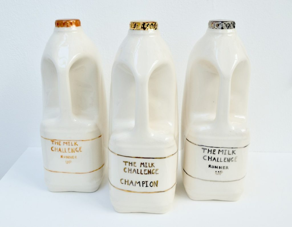 Pictured are three ceramic milk cartons in a row, the central carton stands forward from the others slightly. Each with gold, silver or bronze caps and labels. The bronze carton sits to the left, label reads 'The Milk Challenge, Runner-Up'. Silver sits to the right, also reading The Milk Challenge, Runner-Up. The central carton is gold and reads 'The Milk challenge, Champion'.