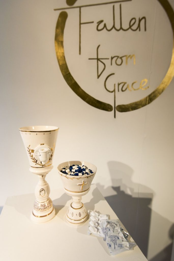 Pictured is an object taken from the project fallen from grace. Two white goblets sit ontop of a plinth, the taller goblet has a cold water tap coming out of the front, the smaller is filled with blue and white medcine capsules. Both goblets are decorated with gold detailing referencing religious orders. The objects look as if offering the eucharist. Behind the goblets the is a gold sign on the wall, it reads fallen from grace and takes the shape of the classic top of the pops logo.