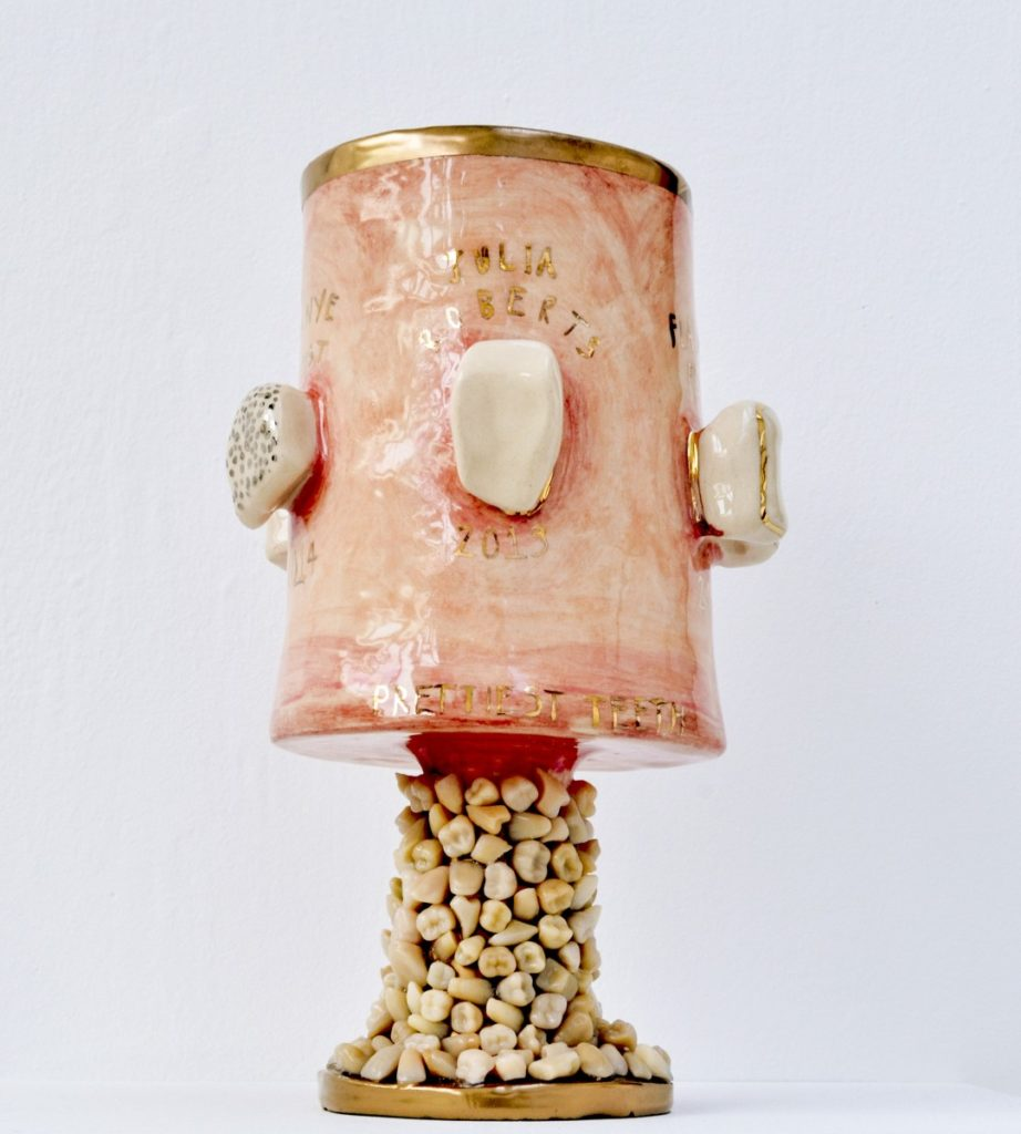 Pictured is a ceramic trophy for celebs with the prettiest teeth. The glossy, fleshy pink goblet has a stem made of hyper realistic teeth. The trophy has gold detailing. Large white ceramic teeth pertrude across the centre of the goblet, each tooth has the name of a celebrity winner above, written in gold lettering.