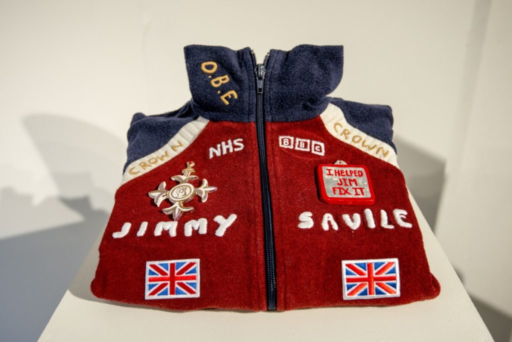 Pictured is a object taken from Fallen from Grace, it is a flannel tracksuit top folded upon a plinth, the tracksuit is red white and blue. Attached are ceramic medals and union jacks. Jimmy Saville is sewn across the front in bold white lettering, in smaller lettering towards the collaring embroidering reads NHS. BBC, O.B.E and Crown.