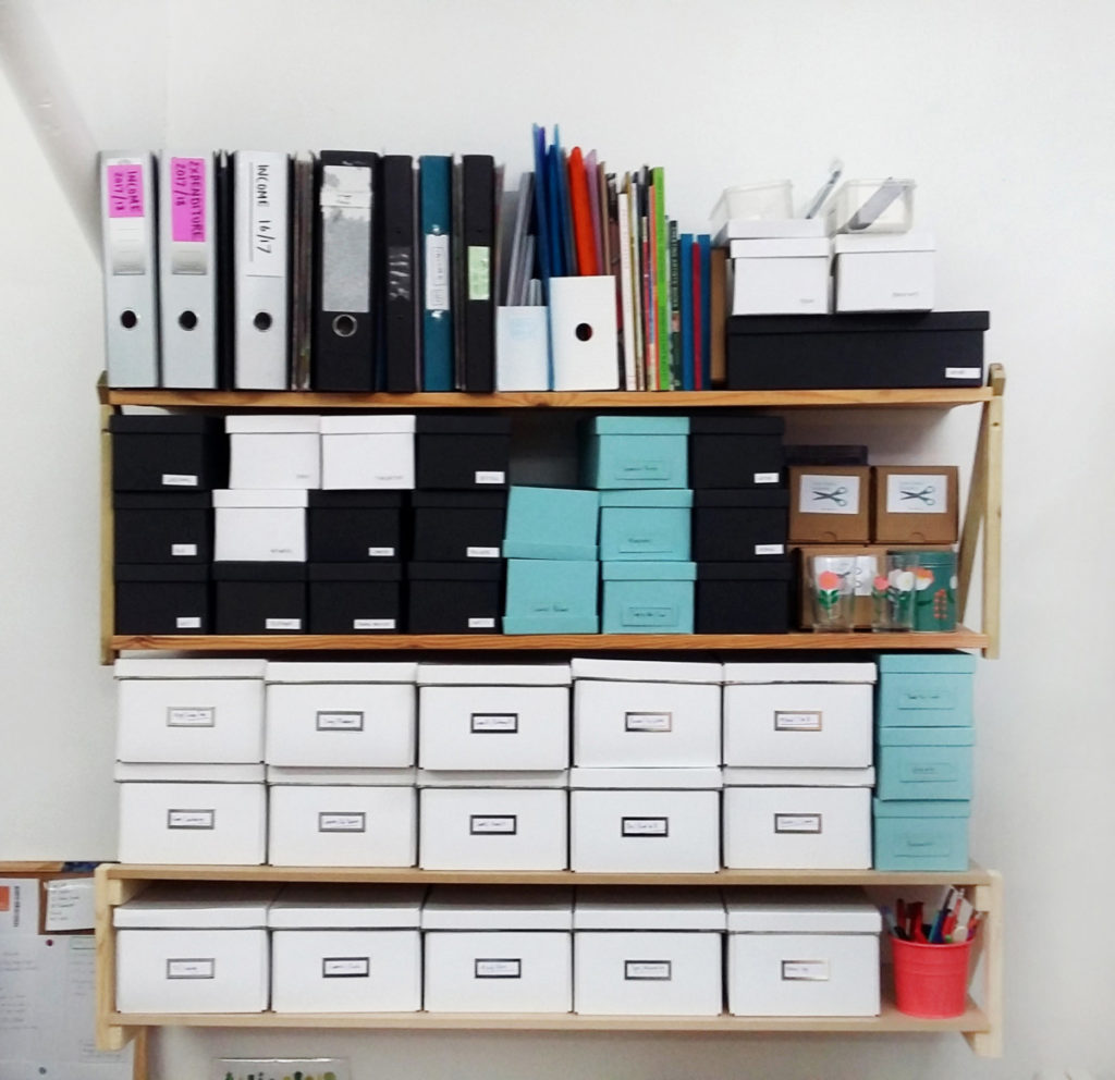 Photograph of four shelves in a studio, with boxes, folders and shelves on.
