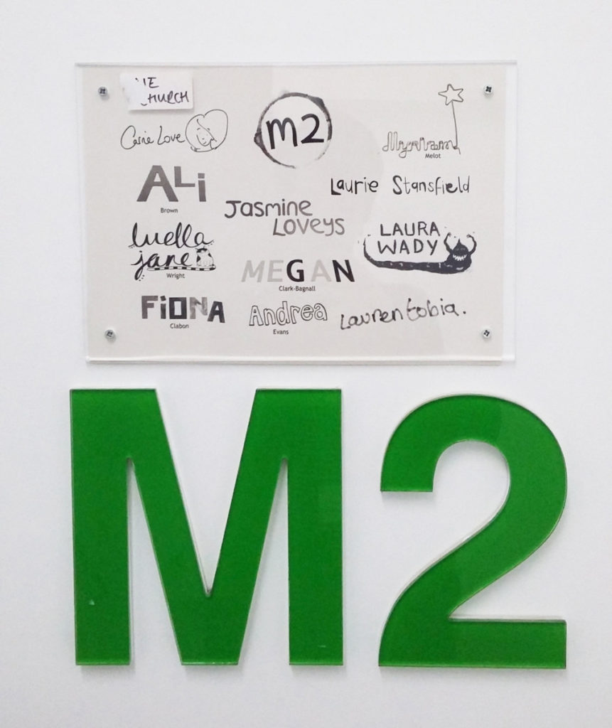 Photograph of a sign with artist names on.
