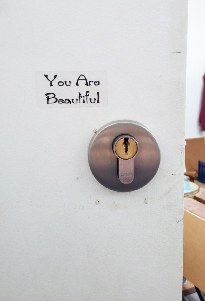Photograph of a small section of a door, including the lock and a sticker saying 'you are beautiful'