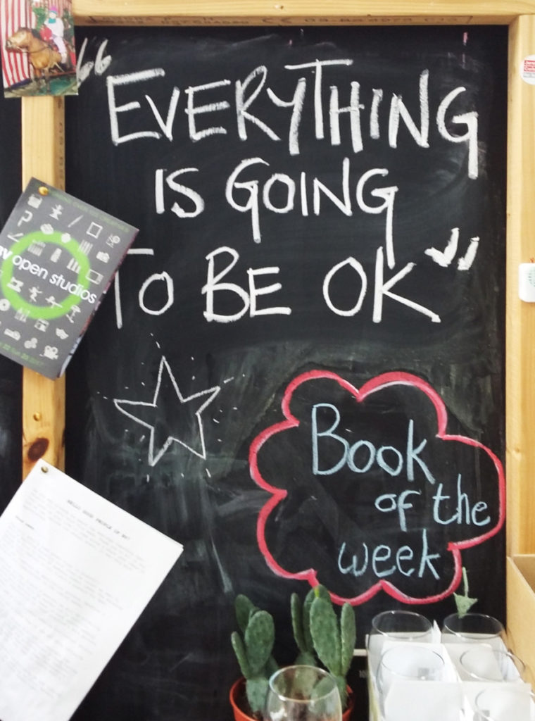 Chalkboard in a studio with 'Everything is going to be okay' written on it in white chalk