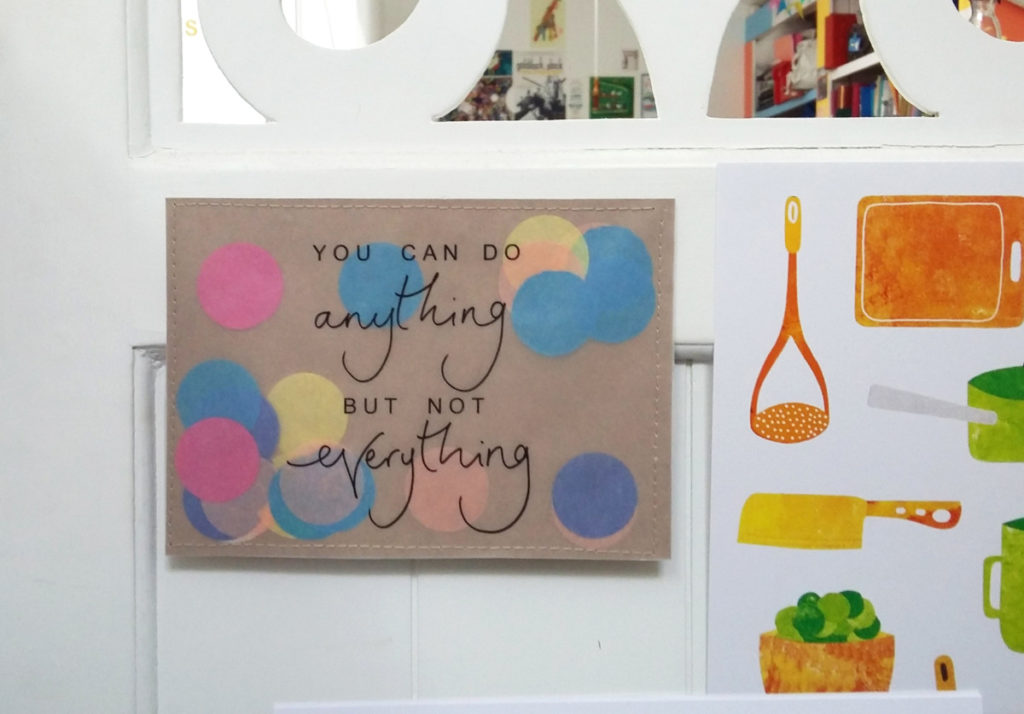 Photograph of a handmade postcard that says 'You can do anything but not everything' on it.